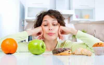 woman-making-a-choice-between-fruit-and-junk-food