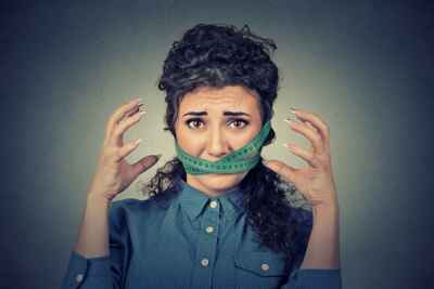 frustrated-woman-with-measuring-tape-over-mouth
