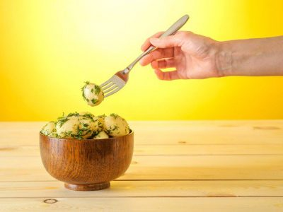 hand-taking-potato-out-of-bowl-of-potatoes-with-fork