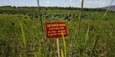 "A warning sign stands in a field contaminated with dioxin near Danang airport, during a ceremony marking the start of a project to clean up dioxin left over from the Vietnam War, at a former U.S. military base in Danang, Vietnam Thursday Aug. 9, 2012. The sign reads; ""Dioxin contamination zone - livestock, poultry and fishery operations not permitted"". The U.S. and Vietnam on Thursday launched a four-year joint effort to clean up dioxin leftover from Agent Orange that was mixed, stored and loaded onto planes at the former U.S. military base, which is now part of Danang's airport. Dioxin can linger in soils and at the bottom of lakes and rivers for generations, entering the food supply through the fat of fish and other animals. (AP Photo/Maika Elan)"